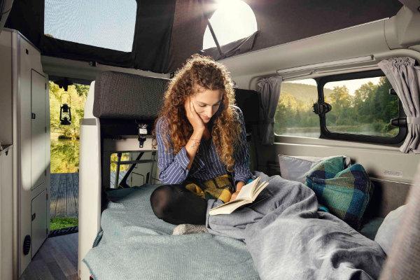 Frau liest Buch im Ford Transit Custom Nugget