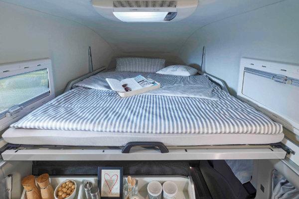 blau-weiss gestreifte Bettwäsche im Schlafbereich des Ford Transit Custom Nuggets