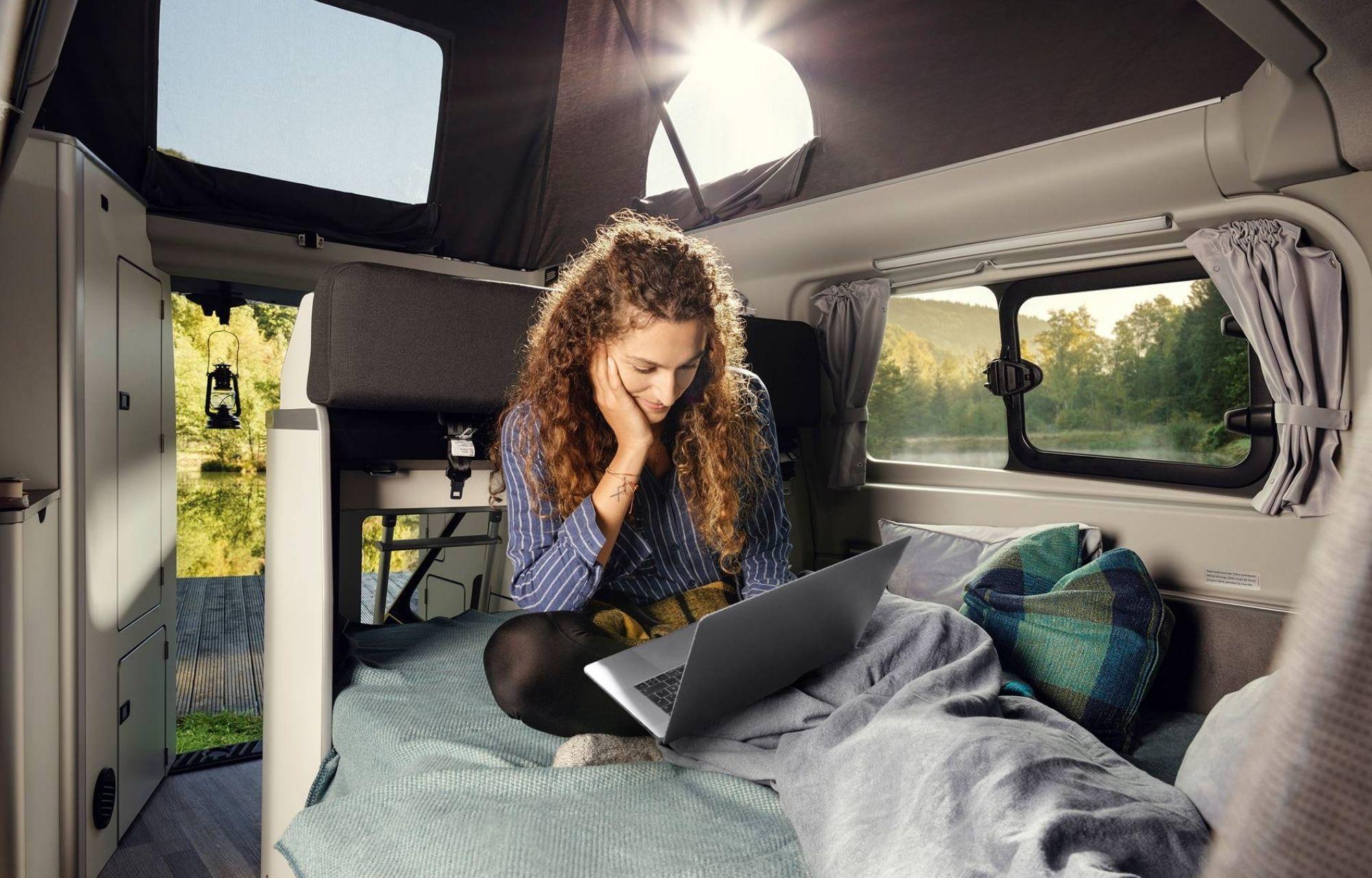Frau liest gemütlich ein Buch im Ford Transit Custom Nugget