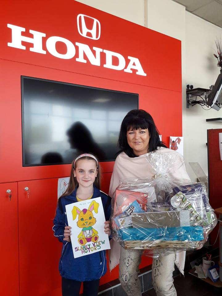 Aoife Walsh collecting her Easter goodies from Margo Doyle